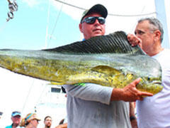 A man holding a mahi mahi with a hand holding up it's top fin, with a guy behind him
