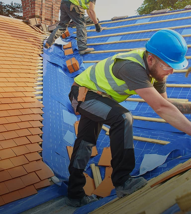 two men in safety vests roofing on a blue tarp